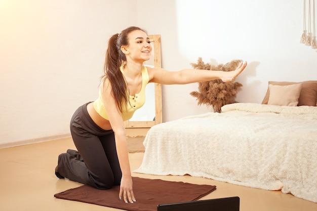 Kobieta ćwiczy w celu utraty wagi. kursy fitness online. patrzy na laptopa
