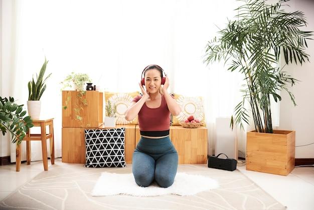 Kobieta ćwiczy w domu. fitness z muzyką