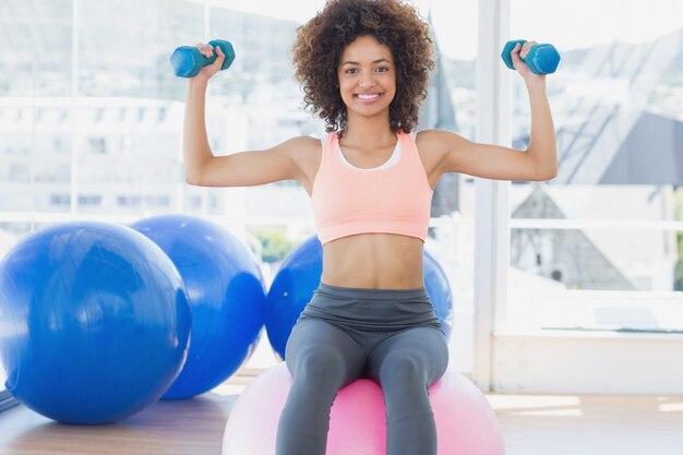 Kobieta ćwiczy z dumbbells na sprawności fizycznej piłce w gym