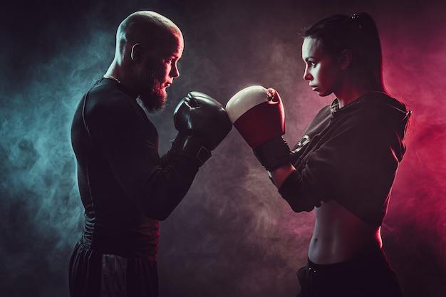 Kobieta ćwiczy z trenerem na lekcji boksu i samoobrony, studio, pali w kosmosie