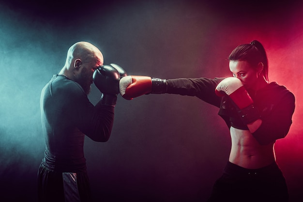 Kobieta ćwiczy z trenerem na lekcji boksu i samoobrony