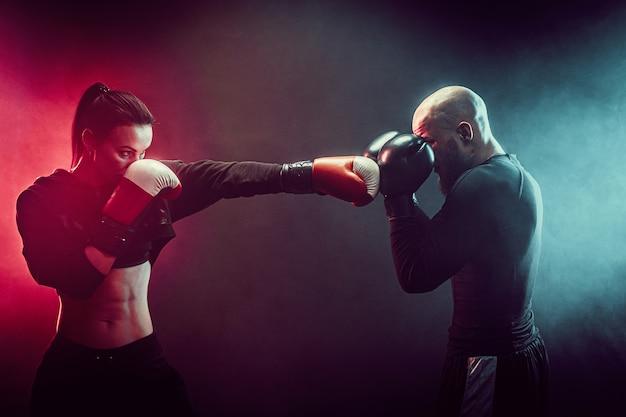 Kobieta ćwiczy z trenerem przy lekcją boksu i samoobrony