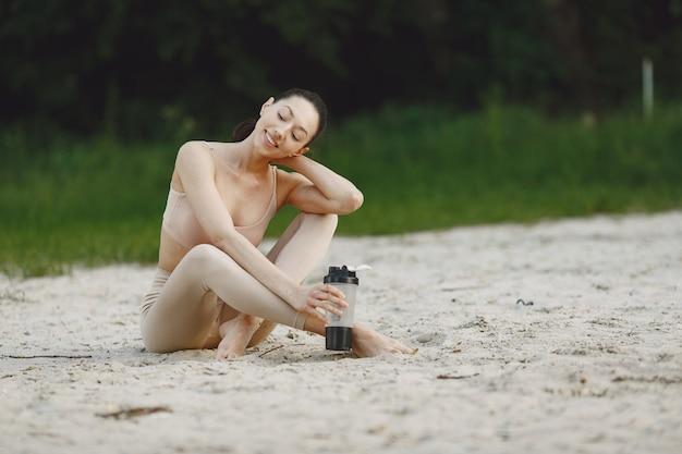 Kobieta ćwiczy zaawansowaną jogę na letniej plaży