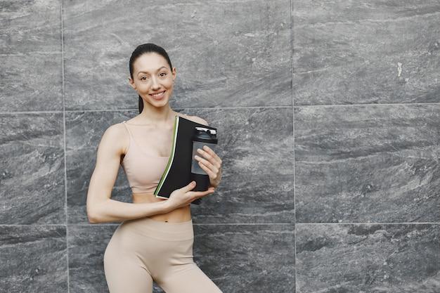 Kobieta ćwiczy zaawansowaną jogę na tle ciemnego muru miejskiego