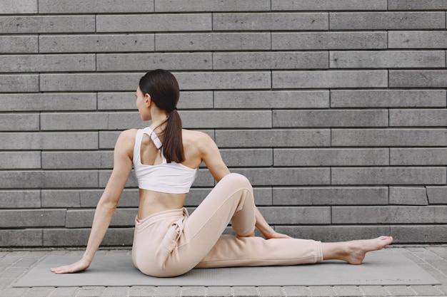 Kobieta ćwiczy zaawansowaną jogę przeciw ciemnej ścianie miejskiej