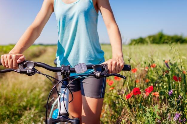 Kobieta cyklista jedzie halnego bicykl w lata kwitnienia polu. zbliżenie kierownicy