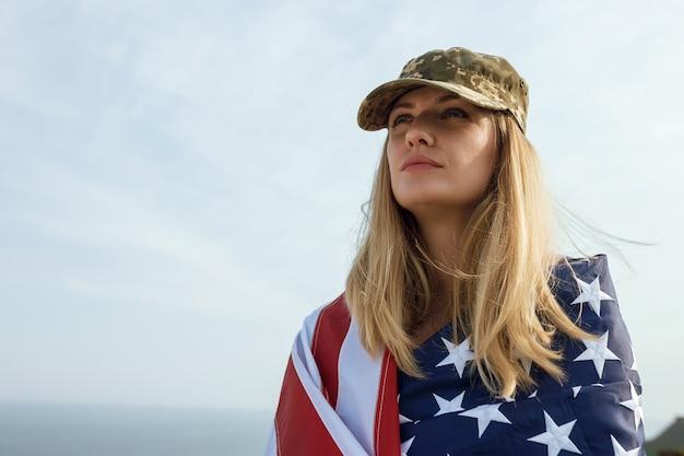 Kobieta cywilna w czapce wojskowej męża. wdowa z flagą stanów zjednoczonych wyszła bez męża. dzień pamięci poległych żołnierzy podczas wojny. 27 maja to dzień pamięci.