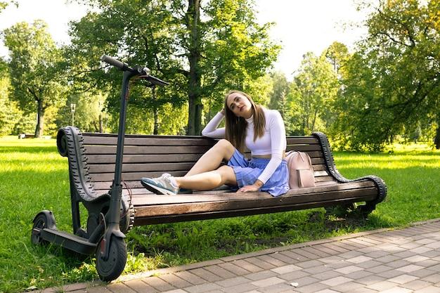 Kobieta czeka na ławce w parku po wycieczce na skuter elektryczny