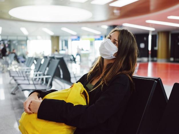 Kobieta czeka na lot na lotnisku żółty plecak maski medycznej