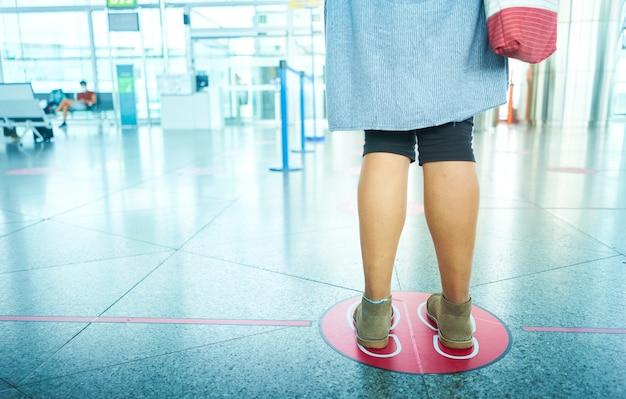 Kobieta czeka na lotnisku, zachowując dystans społeczny. dystans społeczny, którego należy unikać covid 19.