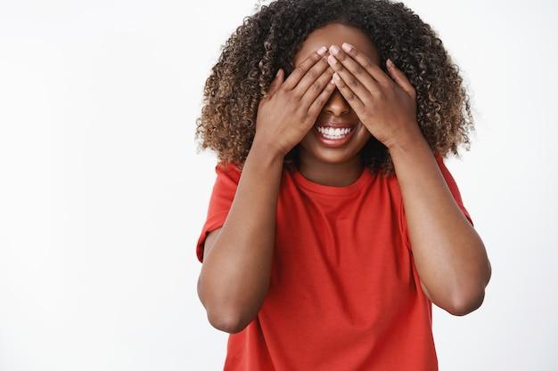 Kobieta czeka na polecenie, aby otworzyć oczy i zobaczyć, co zrobiła niespodzianka koleżanka. portret podekscytowanej i szczęśliwej uroczej kobiety na urodziny w czerwonej koszulce z bliska z dłońmi i uśmiechniętą chętną do podglądania, przewidywania