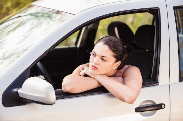 Kobieta czeka na pomoc w pobliżu samochodu zepsutego na poboczu drogi
