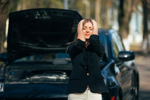 Kobieta czeka na pomoc w pobliżu zepsutego na poboczu samochodu.