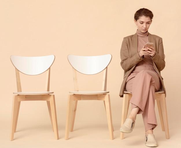 Kobieta czeka w kolejce i przy użyciu telefonu komórkowego
