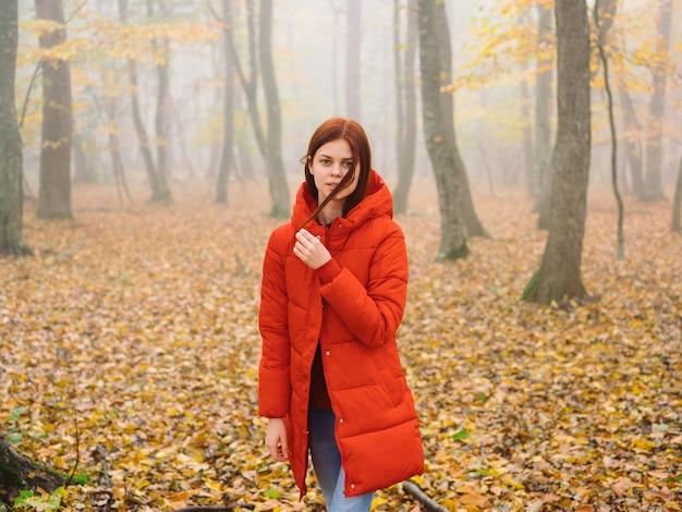 Kobieta czerwona kurtka w lesie jesienią żółte liście chodzić na zewnątrz