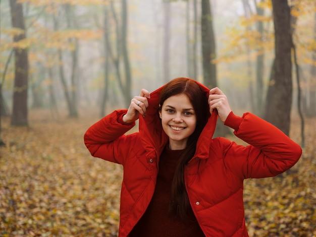 Kobieta czerwona kurtka z kapturem deszcz mgła jesień żółte liście