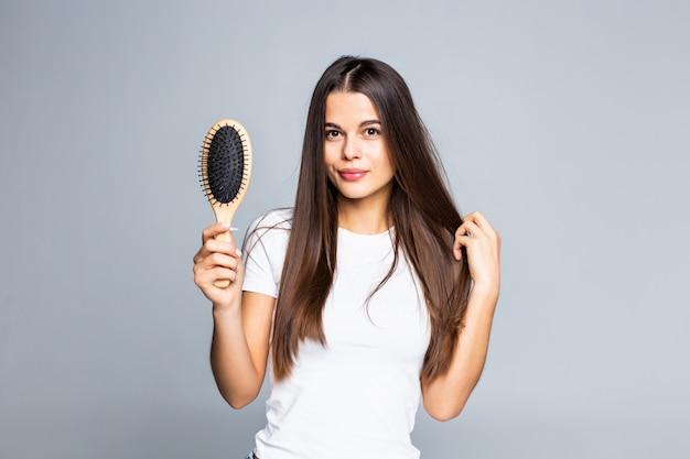 Kobieta czesze jej włosy odizolowywającego na bielu