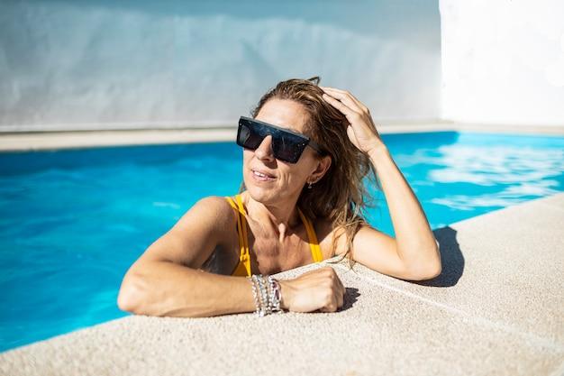 Kobieta Czesze Włosy W Basenie. Ma Na Sobie żółte Stroje Kąpielowe I Czarne Okulary Przeciwsłoneczne Premium Zdjęcia