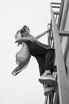 Kobieta czołgająca się po schodach na wietrznym dachu ubrana w długi szyfonowy top, spodnie i sandały. czarny i biały.
