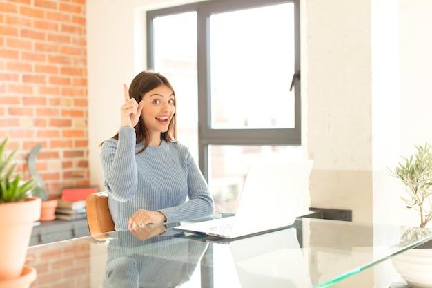 Kobieta czująca się jak szczęśliwy i podekscytowany geniusz po zrealizowaniu pomysłu, radośnie podnoszący palec, eureka!