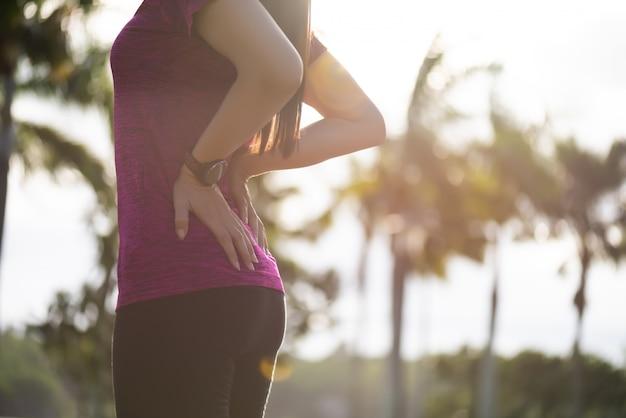 Kobieta czuje ból na jej biodrze i plecy podczas gdy ćwiczący, opieki zdrowotnej pojęcie.