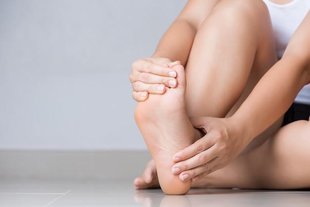 Kobieta czuje ból w stopie w domu. pojęcie opieki zdrowotnej i medycznej.