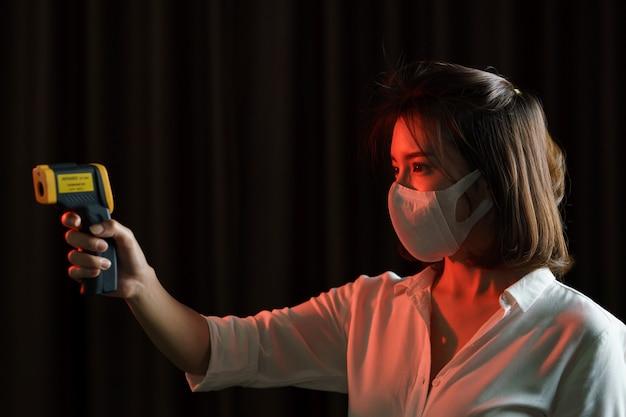 Kobieta czuje się chory noszenie maski ochronne, ręcznie użyć cyfrowy termometr sprawdzanie temperatury.