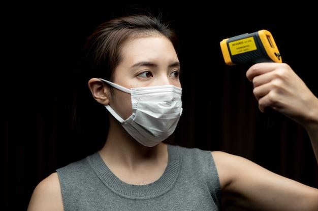 Kobieta czuje się chory noszenie maski ochronne. z ręcznym sprawdzaniem bezpieczeństwa przy bramkach użyj cyfrowego termometru sprawdzającego temperaturę.