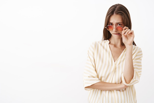 Kobieta czuje się niepewna co do podejrzanej oferty zdjęcia okularów przeciwsłonecznych spoglądającej spod czoła i przygryzającej dolną wargę z powodu niepewności zmartwionych uczuć, wątpliwości i wahań