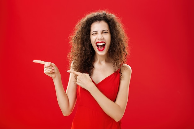 Kobieta czuje się niesamowicie na wielkiej imprezie przyjaciela wskazującego na wejście. stylowa beztroska kręcona kobieta w czerwonej sukni wieczorowej bawiąca się przy basenie mrugająca radośnie uśmiechnięta i wskazująca w lewo.
