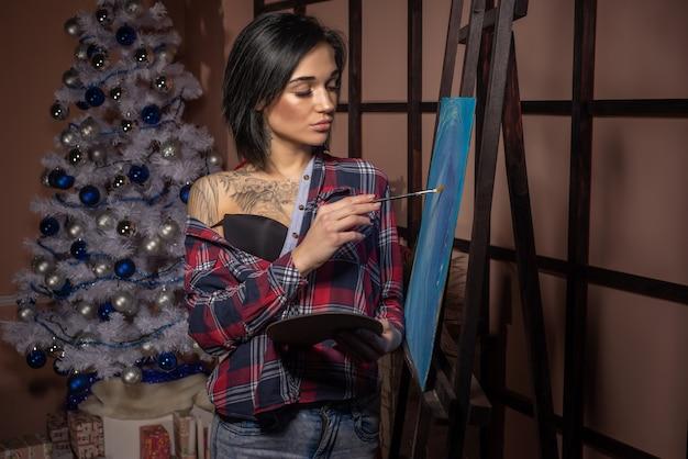Kobieta czuje się samotna podczas świąt bożego narodzenia. maluje obraz