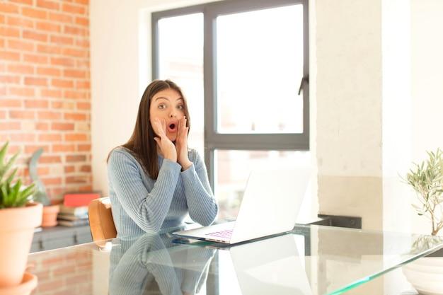 Kobieta czuje się szczęśliwa, podekscytowana i pozytywna, wydając wielki okrzyk z rękami przy ustach, wołając