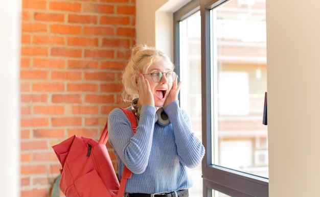 Kobieta czuje się szczęśliwa, podekscytowana i zaskoczona, kobieta patrząca w bok z obiema rękami na twarzy