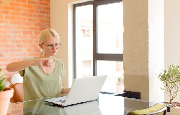 Kobieta czuje się zła, zła, zirytowana, rozczarowana lub niezadowolona, pokazując kciuk w dół z poważnym spojrzeniem