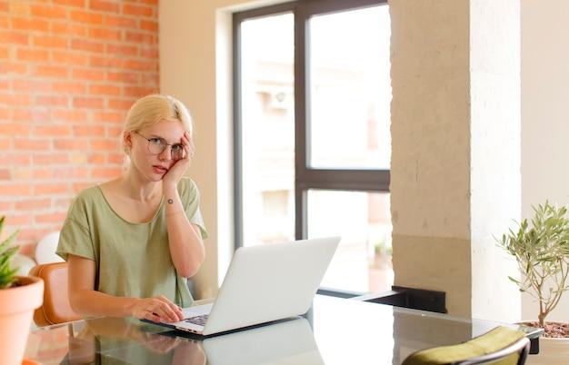 Kobieta czuje się znudzona, sfrustrowana i senna po męczącym, nudnym i żmudnym zadaniu, trzymając twarz dłonią