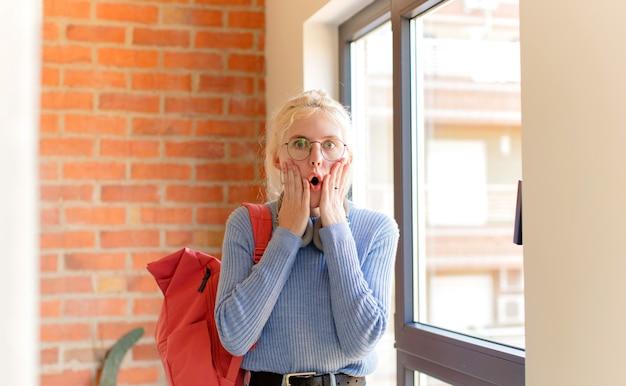 Kobieta czuje się zszokowana i przestraszona, wygląda na przerażoną z otwartymi ustami i rękami na policzkach
