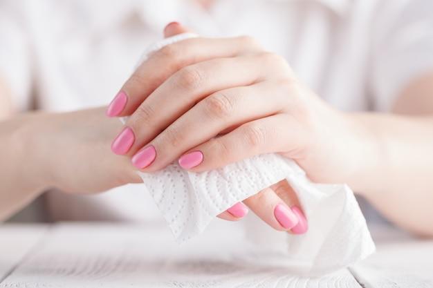 Kobieta czyści jego rękę z tkanką na bielu