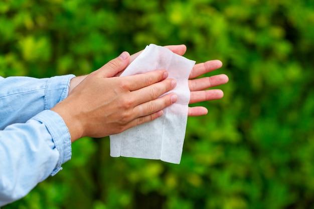 Kobieta czyści jej ręki mokrym chusteczką outdoors