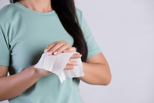 Kobieta czyści jej ręki z tkanką. pojęcie opieki zdrowotnej i medycznej