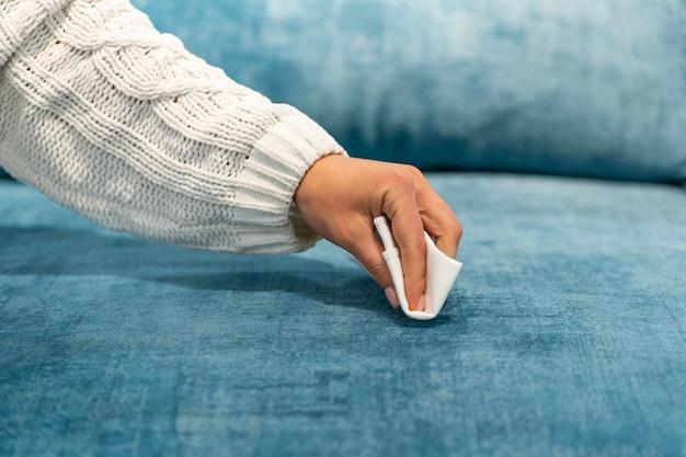 Kobieta czyści niebieską sofę białą szmatką