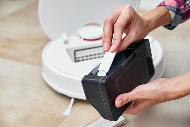 Kobieta czyści pojemnik na kurz w odkurzaczu automatycznym