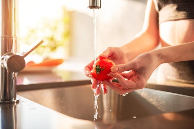 Kobieta czyści pomidory w kuchni w domu oświetlonym słońcem