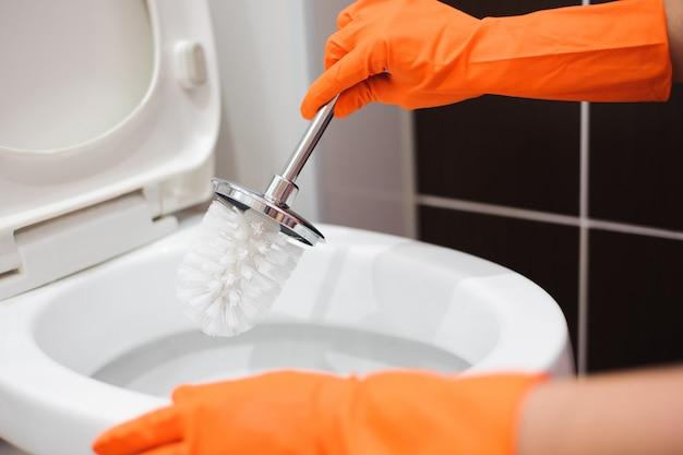 Kobieta czyści toaletę w łazience za pomocą szczotki do szorowania.