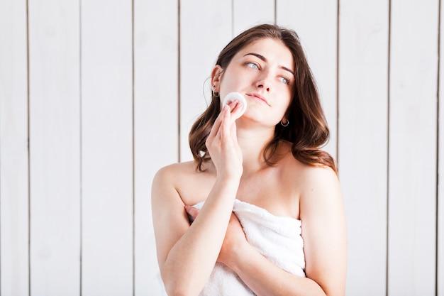Kobieta czyści twarz z bawełnianym ochraniaczem