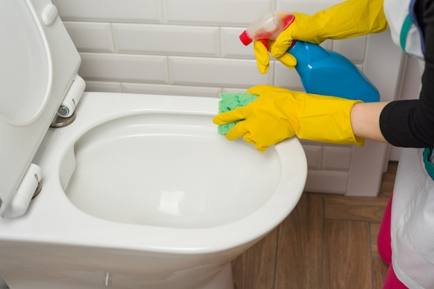 Kobieta czyści w łazience. umyć toaletę.