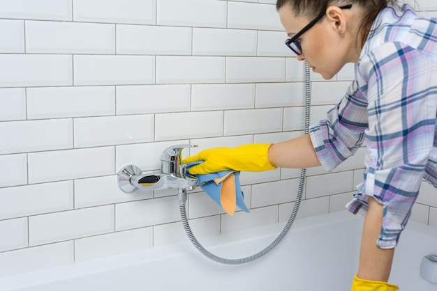 Kobieta czyści w łazience w domu