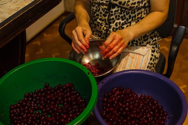Kobieta czyści wiśnie z nasion przed gotowaniem dżemu lub soku
