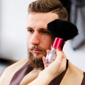Kobieta czyści włosy swojego klienta z jego twarzy