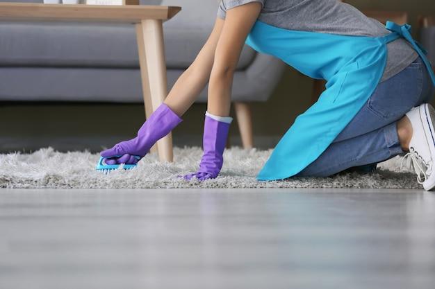 Kobieta czyszczenia dywanów w pokoju