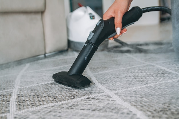 Kobieta czyszczenia dywanów za pomocą odkurzacza parowego